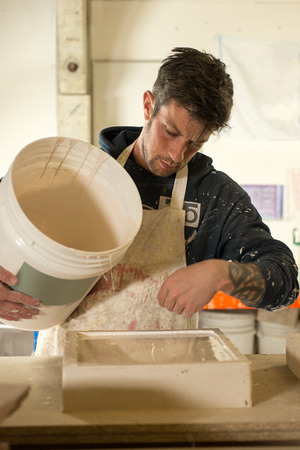 plaster of paris: A man in plaster-splattered clothing and apron inspects freshly laid plaster on a rectangular mold Stock Photo