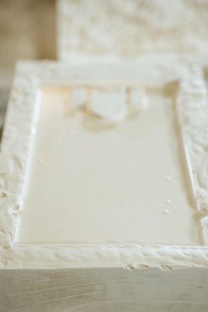 A small rectangular mold filled with plaster