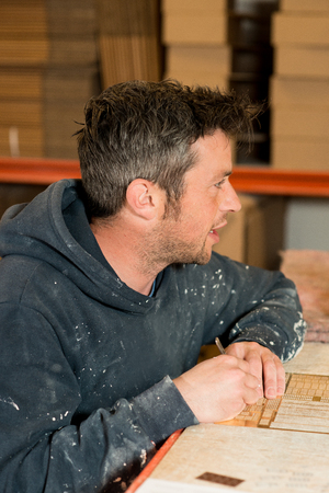 drafting table: A stubbly caucasian male wearing a paint-splattered dark hoodie, working on a drafting table and having a conversation.