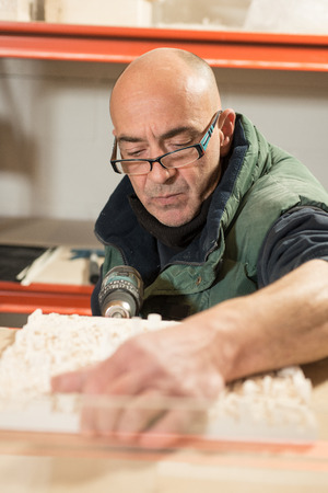 electric drill: A man in thick clothing and eyeglasses perforating one side of a plaster model using an electric drill
