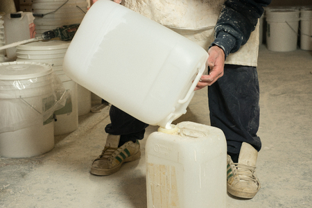 transfering: A man pouring liquid plaster resin into a large white plastic container