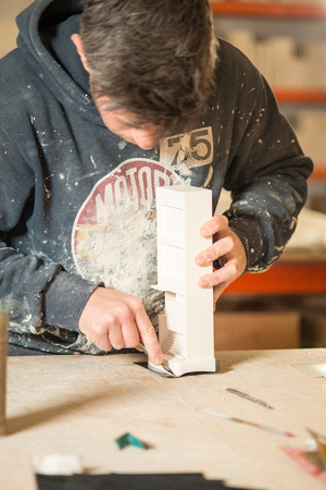drafting table: A man in paint-splattered hoodie trimming a section of a plaster model building using a utility knife
