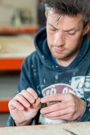 stubbly: A stubbly caucasian male in paint-splattered carefully examining a part of product.