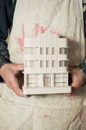 plaster of paris: A plaster scale model of a known architectural building held with two hands of a person.