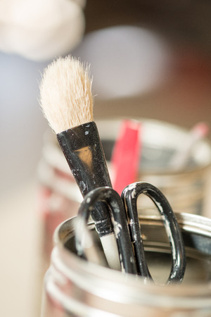 bristles: Close-up of a used paint brush with worn bristles and a pair of scissors in an open canister Stock Photo