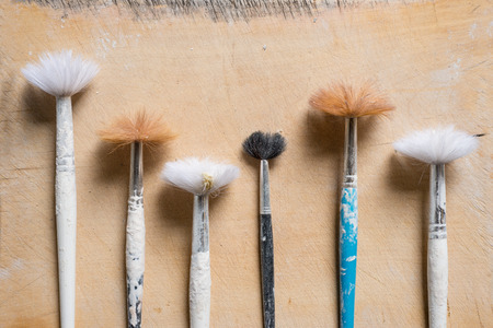 Paintbrushes with plaster-splattered handles and worn bristles individually positioned vertically and laid on a worn wooden surface Stock Photo