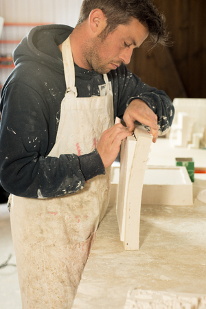 stubbly: A stubbly man in scruffy work clothing carefully separating a plaster model from its mold.