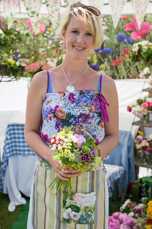 A pretty female gardener holding a bunch of flowers standing in front of her stand at a summer country fayre