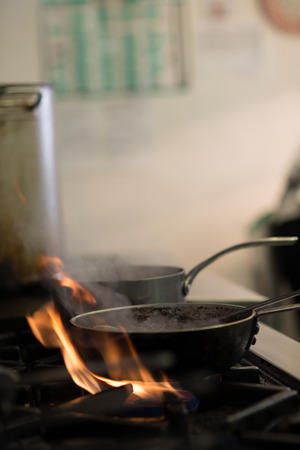 gas burner: Smoking pans on gas burner flames in a kitchen