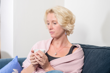 A casually dressed middle aged blonde woman sits at home cradling a hot drink and thinking about something. She looks serious or even sad and in need of comfort. Copy space Stock Photo