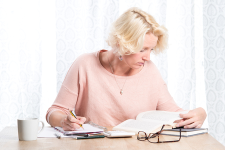 casually dressed: A blonde woman casually dressed in a pink jumper with necklace researches a book whilst writing in a pad with a pencil.  She sits at a wooden table in front of white curtains with a mug of drink and calculator nearby. Copy Space