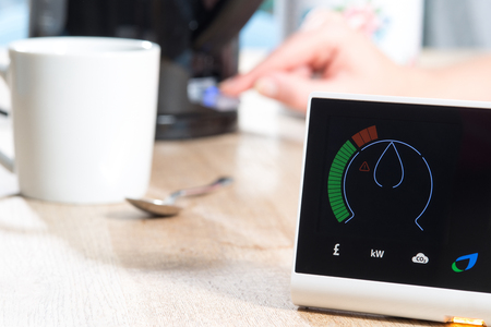 A smart meter is displayed on a  wooden surface near mug and spoon and a kettle which is being switched on by a hand. The meter is giving a digital reading of energy consumption. COPY SPACE