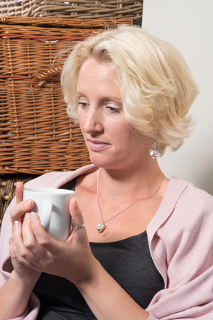 wistful: A middle aged blonde woman sits next to wicker boxes on a sofa or couch, holding a mug in both hands and looking satisfied with a wsmall smile on her face while she thinks