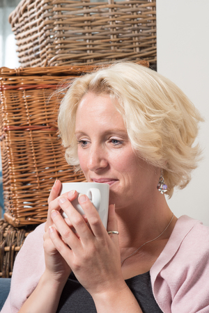 wistful: A middle aged blonde woman sits next to wicker boxes on a sofa or couch, holding a mug in both hands close to her mouth. She smiles with satisfaction or comfort Stock Photo