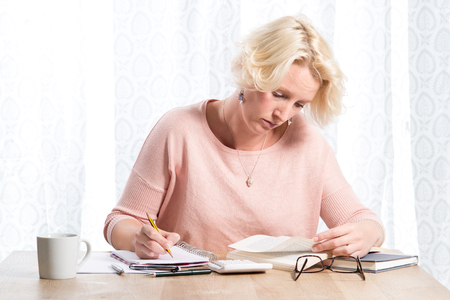 casually dressed: A blonde woman casually dressed in a pink jumper with necklace researches a book while writing in a pad with a pencil.  She sits at a wooden desk with a mug of tea or coffee and calculator nearby. Copy Space
