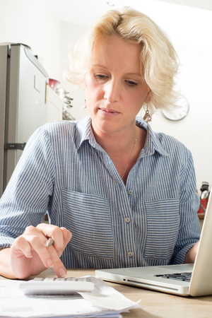 Woman looking worried while using a calculator and laptop in home kitchen environment Stock Photo