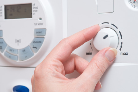 appears: A hand spins the dial on a white boiler. It appears to be turning towards the MAX setting. Other buttons and a digital display are visible in the background Stock Photo