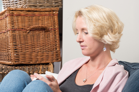 wistful: A middle aged blonde woman sits next to wicker boxes on a sofa or couch, holding a mug in both hands and looking thoughtful