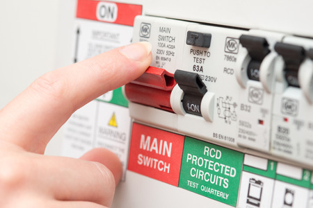 A finger is about to switch off a large red MAINS switch on an RCD circuit breaker board Stok Fotoğraf