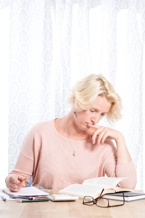 casually dressed: Portrait shot of a casually dressed blonde woman sitting at home working at a wooden desk. She is writing in a pad and reading from a book. She has removed her glasses and is thinking intently. Copy Space Stock Photo