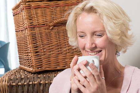 wistful: A middle aged blonde woman holding a mug in both hands smiles and laughs while looking wistful