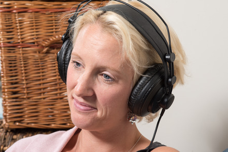 A middle aged blonde woman sits at home, wearing large black headphones. She tilts her head and smiles while looking wistful