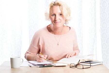 A blonde woman reading from books and writing in a pad smiles to camera. She sits at a wooden desk at home with a mug of drink and looks relaxed and happy. Copy Space