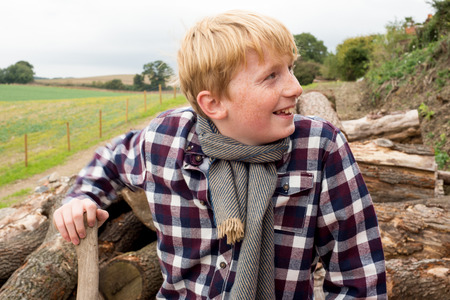 plaid shirt: Boy in plaid shirt, scarf, and hat holding an axe in front of a pile of firewood in a farm Stock Photo