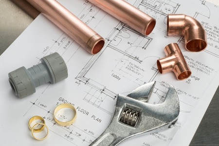 copper pipe: Various plumbers tools and plumbing materials including copper pipe, elbow joint, wrench and spanner. shot on top of architects house plans on a bright stainless steel background.