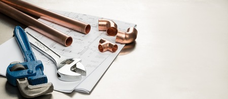 copper pipe: Various plumbers tools and plumbing materials including copper pipe, elbow joint, wrench and spanner. shot on a bright stainless steel background. Shot in banner format with space for text or copy. Stock Photo