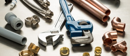 Verschiedene Klempner Werkzeuge und Sanitär-Materialien einschließlich Kupferrohr, Ellenbogengelenk, Schraubenschlüssel und Schraubenschlüssel. Schuss auf einem hellen Edelstahl Hintergrund.