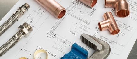 Divers plombiers outils et matériaux de plomberie y compris les tuyaux de cuivre, coude, clé et clé. tir au-dessus des plans d'architectes de maison sur un fond en acier inoxydable brillant.