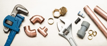 copper pipe: Various plumbers tools and plumbing materials including copper pipe, elbow joint, wrench and spanner. shot on a bright stainless steel background.