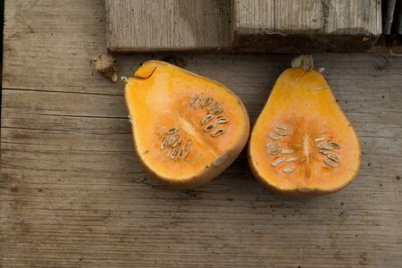 insides: Overhead of halves of a squash with insides exposed on a wooden surface.
