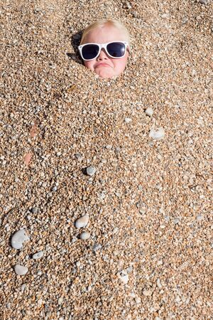 head stones: A young blonde girl in sunglasses frowns jokingly to camera from beneath the pebbles of a beach. Everything except her head has been buried under the stones