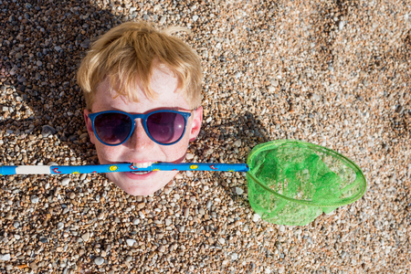 head stones: A young boy with freckles, sunglasses and strawberry blond hair holds a childs fishing net in his teach. His body has been buried under stones on the beach and only his head is protruding