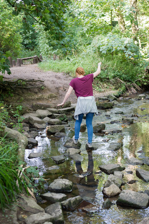 A young red haired girl carefully crosses natural stepping stones on a shallow river through English woodland