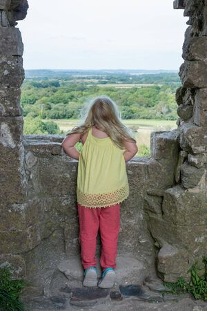 peer to peer: a small blonde girl stands on tip toe to peer over the stone wall of a structure at the lush green countryside in the distance Foto de archivo