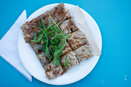 Overhead shot of a crepe in bite-size pieces served in a paper plate with a plastic fork and topped with greens