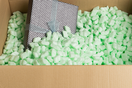 cushioning: Wrapped present with ribbon in a cardboard box filled with Polystrene loosefill