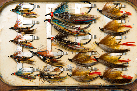 Very old salmon fishing flies in an open fly box
