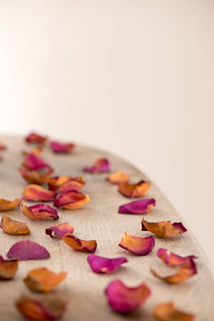 loosely: Wooden tabletop with red rose petals scattered loosely. Space for product or text.