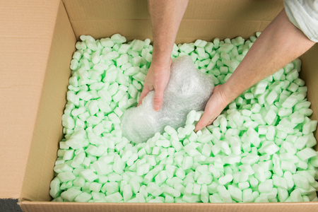 cushioning: Hands placing a bubble wrapped parcel in polystyrene loosefill.
