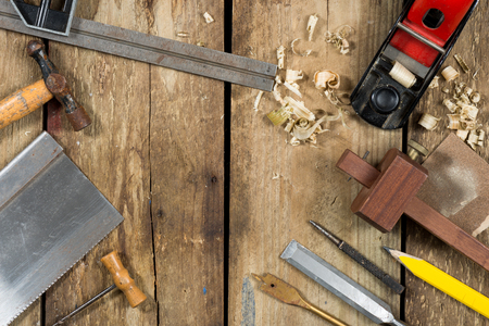 auger: Old woodworking tools. Tools include a bradle, punch, saw, hammer, gauge, ruler, drill and drill bit an auger, chisel, pencil and wood plane