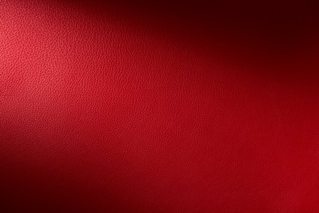 Close up of a section of a Vibrant red leather swatch showing grain and a shaft of light across Stock Photo