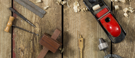 auger: Old woodworking tools shot in website banner format. Tools include a bradle, punch, gauge, ruler, drill and drill bit an auger and wood plane