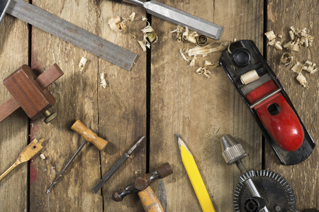 auger: Old woodworking tools. Tools include a bradle, punch, hammer, gauge, ruler, drill and drill bit an auger, chisel, pencil and wood plane Stock Photo
