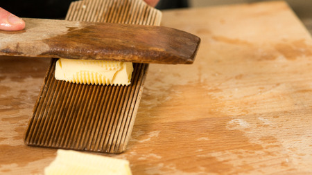 A pat of butter kneaded and rolled grooved wooden paddles Stock Photo