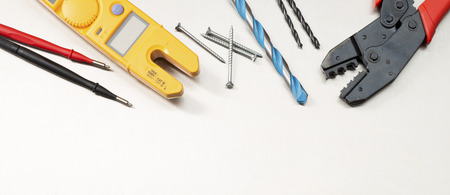 Various electrician tools and components including a multimeter, wirecutters, drill bits, switches and sockets. Web banner format.