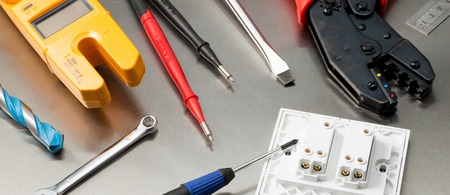 wirecutters: Various electrician tools and components including a multimeter, screwdrivers, wirecutters, drill bits, switches and sockets. Web banner format. Stock Photo
